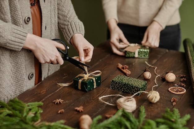Primo piano di due donne irriconoscibili che avvolgono i regali di natale in uno spazio di copia di un tavolo in legno rustico