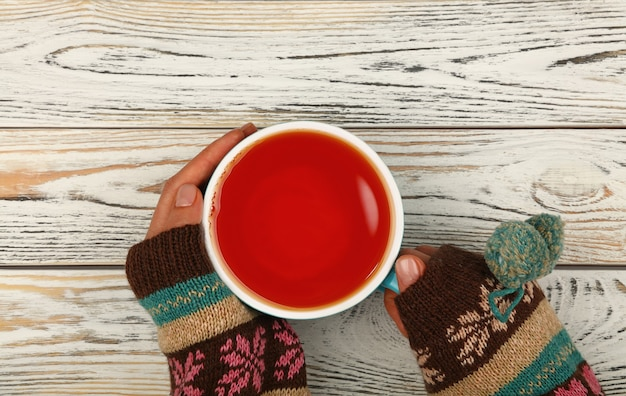 Chiudere fino a due mani di donna tenere e abbracciare grande tazza piena di tè nero o frutta rossa su bianco tavolo in legno, vista dall'alto, direttamente sopra