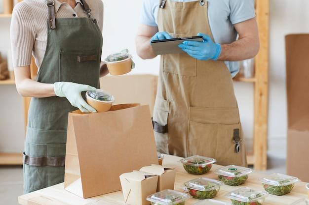 Primo piano di due lavoratori in guanti protettivi che lavorano nel servizio di consegna che imballano il cibo in sacchetti di carta
