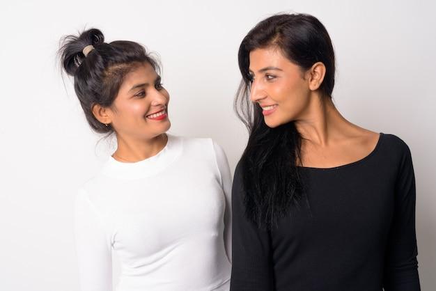 Primo piano di due giovani belle donne persiane insieme come sorelle isolate