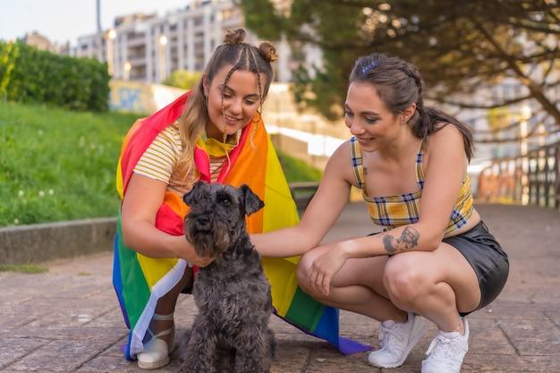 Primo piano di due giovani donne caucasiche che tengono una bandiera dell'orgoglio lgbt in un parco accanto al loro cane nero