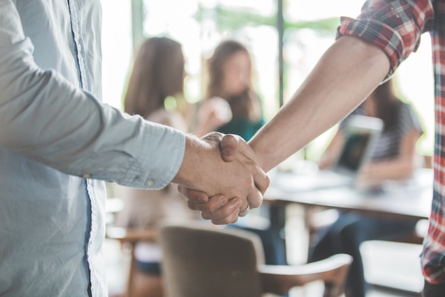 In prossimità di due giovani maschi business partner stringono la mano in un caffè