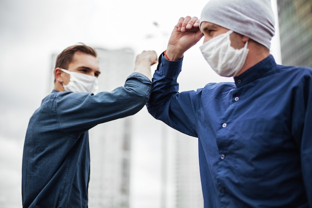 Avvicinamento. due giovani si salutano con i gomiti. concetto di tutela della salute