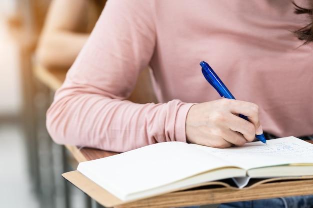 Primo piano degli studenti universitari che scrivono una nota sul taccuino in classe mentre ascoltano e studiano la lezione. primo piano delle mani della donna che scrivono su un blocco note posizionato su una scrivania in legno