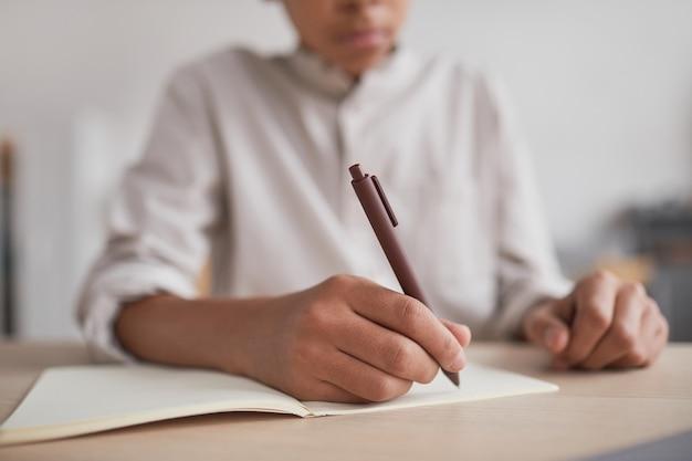 Primo piano di un ragazzo afro-americano irriconoscibile che fa i compiti e scrive sul taccuino mentre è seduto alla scrivania, concentrarsi sulla penna che tiene in mano, spazio di copia