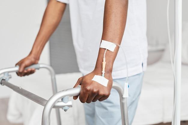 Primo piano di un uomo afroamericano irriconoscibile che si appoggia al deambulatore in ospedale, si concentra sul catetere a goccia iv in mano, copia spazio