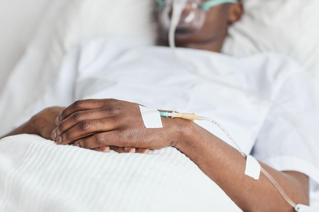 Primo piano di un uomo afroamericano irriconoscibile sdraiato in un letto d'ospedale bianco con particolare attenzione al catetere a goccia iv in mano, spazio di copia