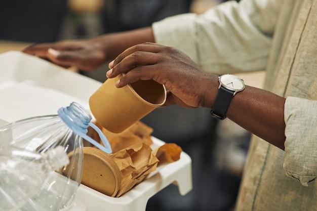 Primo piano di irriconoscibile uomo afro-americano che mette il bicchiere di carta nel cestino per la raccolta differenziata in ufficio, copia dello spazio