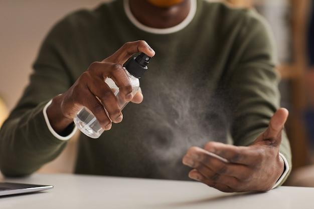 Primo piano di irriconoscibile uomo afro-americano che disinfetta le mani con spray mentre si lavora alla scrivania in ufficio, copia dello spazio
