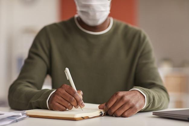 Close up irriconoscibile afroamericano uomo che indossa la maschera durante la scrittura nel pianificatore alla scrivania in ufficio, copia dello spazio