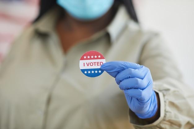 Close up irriconoscibile donna afro-americana azienda ho votato adesivo mentre si sta in piedi al seggio elettorale il giorno delle elezioni post-pandemia, spazio di copia