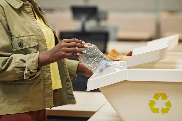 Primo piano di irriconoscibile donna afro-americana mettendo la bottiglia di plastica nel cestino per la raccolta differenziata in ufficio, copia dello spazio