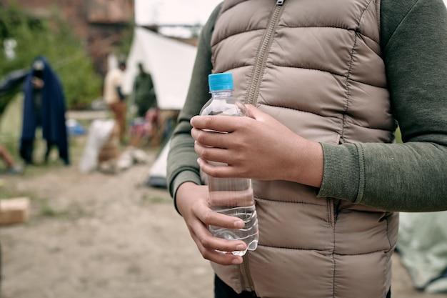 Primo piano di una ragazza nera irriconoscibile con un giubbotto caldo in piedi con una bottiglia d'acqua contro il campo di migranti