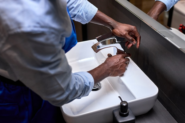 Primo piano della mano dell'idraulico nero irriconoscibile che cerca di aprire un rubinetto dell'acqua in bagno