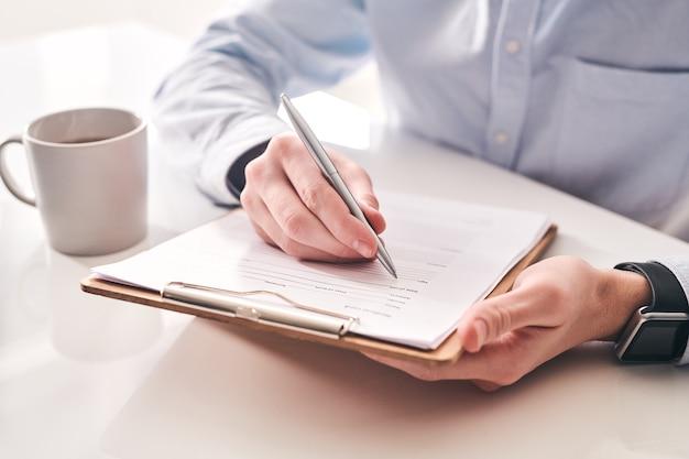 Primo piano di uomo d'affari irriconoscibile seduto al tavolo con una tazza di tè e prendere appunti nel modulo di domanda