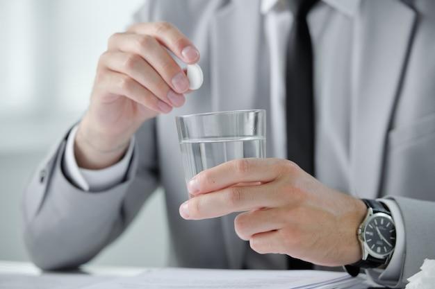 Primo piano di uomo d'affari irriconoscibile in orologio da polso sciogliere la pillola in acqua mentre soffre di sbornia mattutina sul posto di lavoro