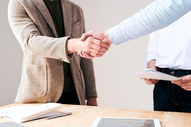 Primo piano di uomini d'affari irriconoscibili che stringono la mano durante l'avvio di una nuova collaborazione