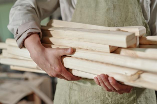 Close-up di un irriconoscibile falegname in grembiule che trasportano mucchio di assi di legno per fare mobili
