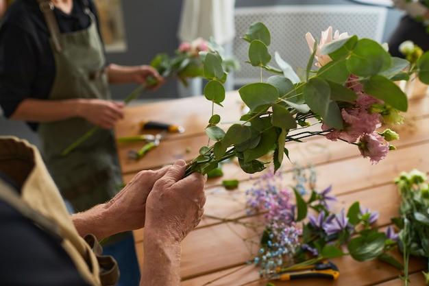 Primo piano di un fiorista irriconoscibile che presenta composizioni floreali in un accogliente spazio di copia dell'officina