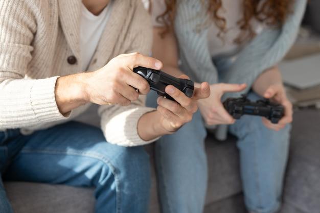 Primo piano di amici irriconoscibili in abbigliamento casual usando i joystick mentre si divertono con il videogioco