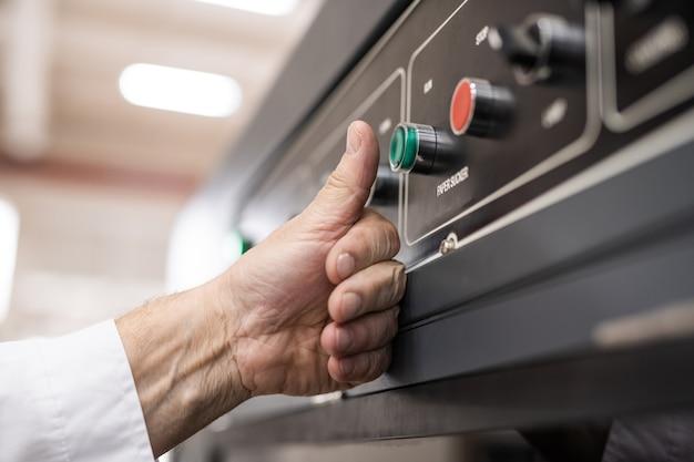 Primo piano dell'operatore della macchina irriconoscibile che spinge il pulsante durante il lancio della linea di produzione in fabbrica