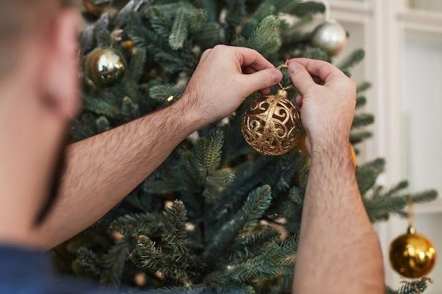 Primo piano di un uomo irriconoscibile che appende decorazioni sull'albero di natale