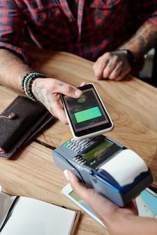 Primo piano di un uomo irriconoscibile seduto al tavolo e pagando con carta online su smartphone nella caffetteria