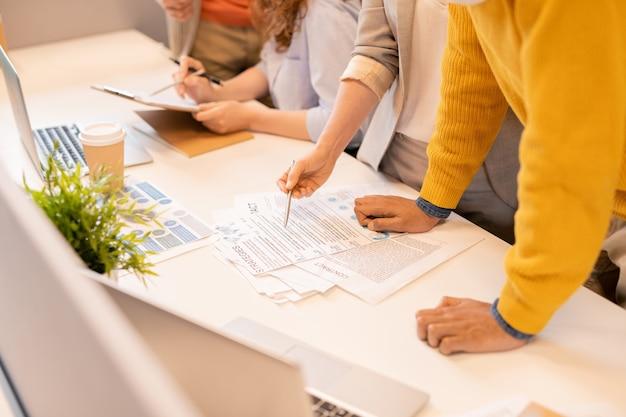 Primo piano di specialisti di marketing irriconoscibili in piedi alla scrivania ed esaminando il contratto e il rapporto di lavoro