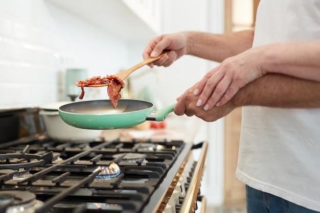 Close up irriconoscibile coppia matura cucinare la colazione insieme nella cucina domestica con focus sulle mani tenendo la padella, copia dello spazio