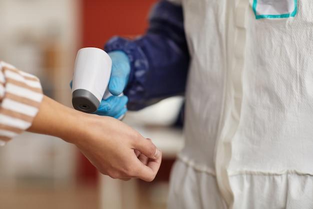 Chiuda in su del lavoratore medico irriconoscibile che controlla la temperatura con il termometro senza contatto che indica alle mani femminili, lo spazio della copia