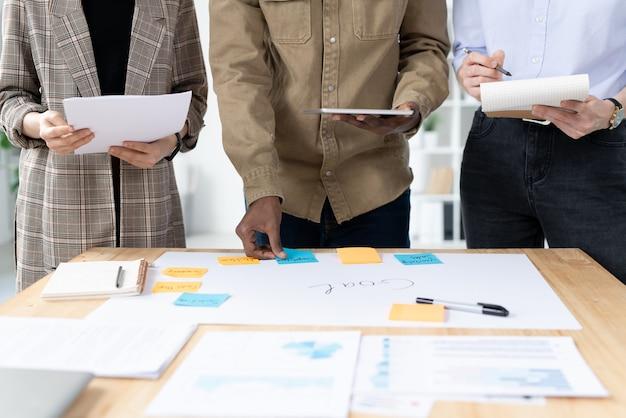 Primo piano del team di marketing multietnico irriconoscibile che crea un piano di attività per raggiungere l'obiettivo in ufficio