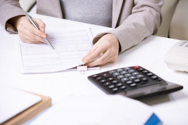 Primo piano della donna irriconoscibile dell'ufficio in giacca che si siede al tavolo con la calcolatrice e il riempimento del modulo finanziario