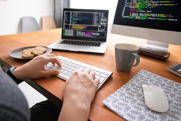 Primo piano del programmatore irriconoscibile seduto alla scrivania con caffè e biscotti e creazione di codice