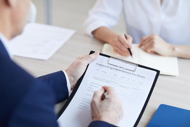 Close up irriconoscibile imprenditore senior firma contratto di contratto durante la riunione in ufficio