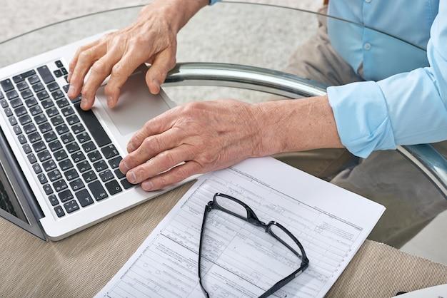 Primo piano di un uomo anziano irriconoscibile seduto al tavolo vetroso e utilizzando il computer portatile durante la compilazione del modulo di richiesta online