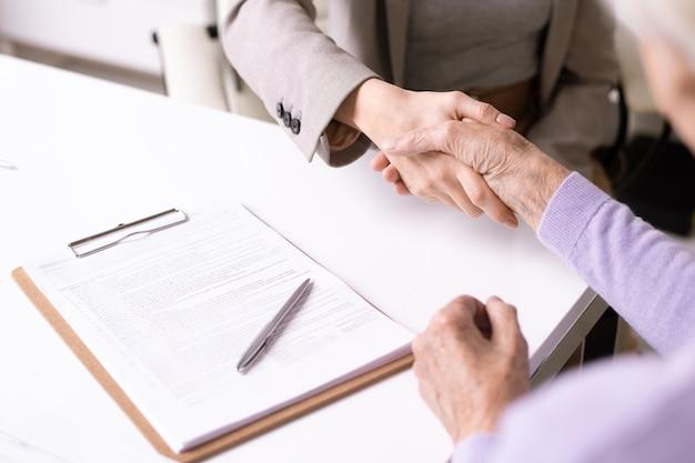 Primo piano di handshake irriconoscibile dell'assistente sociale con la signora anziana dopo la firma del documento