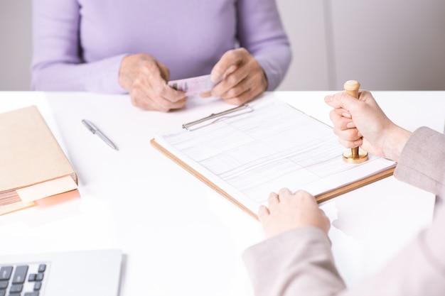 Primo piano di carta da timbratura specialista irriconoscibile durante la certificazione per la signora senior