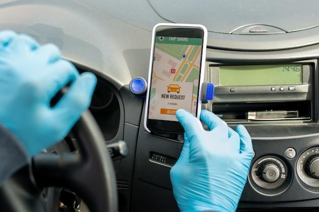 Primo piano del tassista irriconoscibile in guanti che accetta la richiesta di taxi tramite app mobile sullo smartphone durante la pandemia