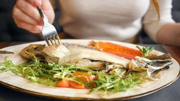 Primo piano di una donna irriconoscibile che mangia bistecca di pesce con coltello e forchetta.