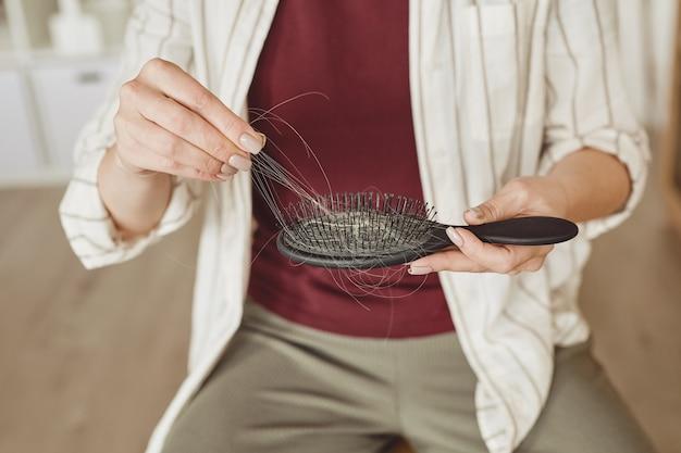 Close up irriconoscibile donna tenendo la spazzola piena di capelli, perdita di capelli e concetto di alopecia, copia dello spazio