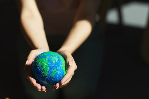 Primo piano della donna irriconoscibile che tiene il modello del pianeta nelle mani alla luce del sole, salvando il concetto di terra