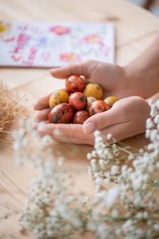 Primo piano di donna irriconoscibile che tiene piccole uova colorate mentre si prepara per le vacanze di pasqua