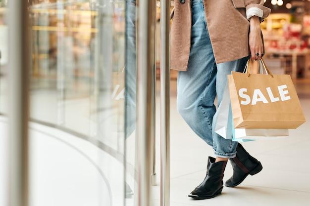 Primo piano di donna irriconoscibile in jeans in piedi con le borse della spesa nel centro commerciale, concetto di sconti