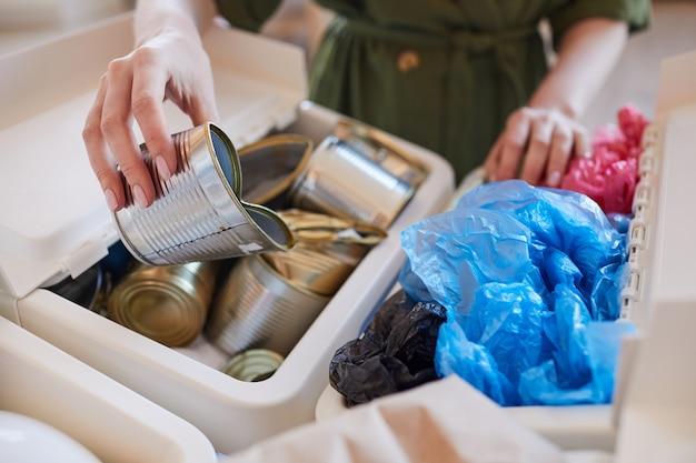 Chiuda in su della donna irriconoscibile che mette le lattine di metallo scartate nel cestino della spazzatura mentre smistano i rifiuti a casa