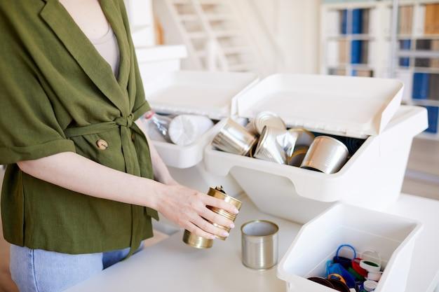 Chiuda in su della donna irriconoscibile che mette le lattine di metallo scartate in un contenitore di plastica durante lo smistamento dei rifiuti a casa per il riciclaggio