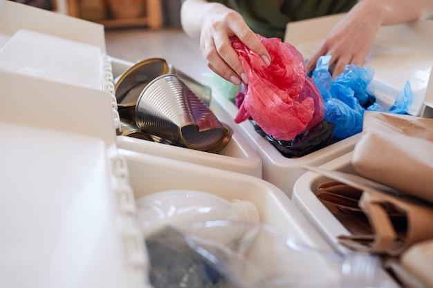 Primo piano di donna irriconoscibile che mette il sacchetto di plastica scartato nel cestino della spazzatura mentre si smistano i rifiuti a casa