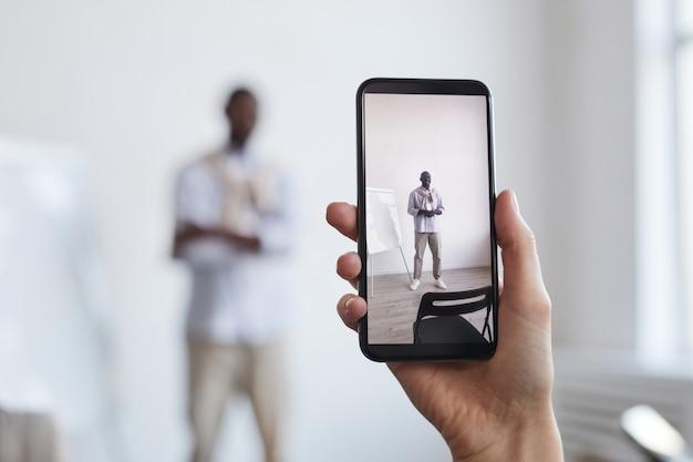 Primo piano di una donna irriconoscibile che scatta foto di un uomo d'affari afroamericano in piedi accanto alla lavagna, si concentra sullo schermo dello smartphone, copia spazio