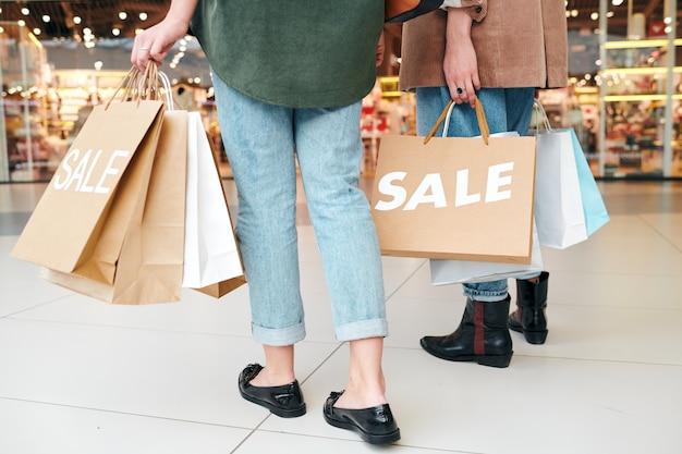 Primo piano di donna irriconoscibile con sacchetti di carta che vanno a fare shopping con un amico nel centro commerciale