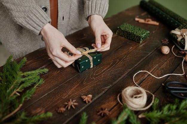 Primo piano di una donna irriconoscibile che avvolge il regalo di natale allo spazio della copia di un tavolo in legno rustico
