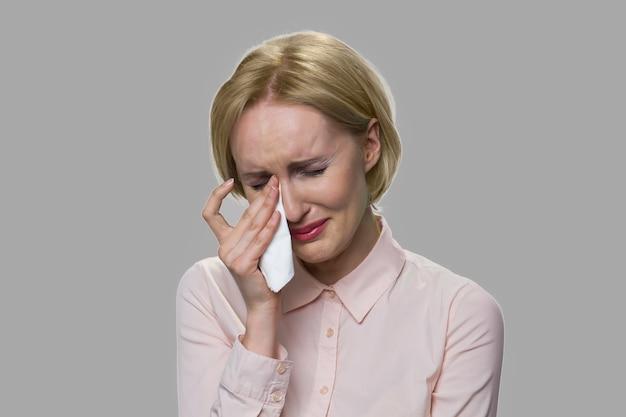 Close up upset giovane donna sta piangendo. ha sottolineato la donna di mezza età sta piangendo su sfondo grigio. problema sul lavoro.